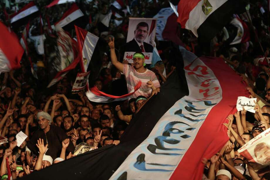 Supporters of Egypt's ousted President Mohammed Morsi hold a large Egyptian national flag outside a  mosque, where  they have installed a camp and hold daily rallies at Nasr City in Cairo. Photo: Hassan Ammar / Associated Press