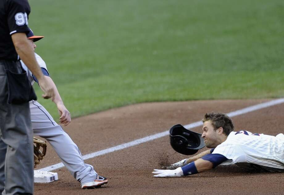 Brian Dozier slides in safely to third with a triple as Matt Dominguez awaits the throw. Photo: Hannah Foslien, Getty Images