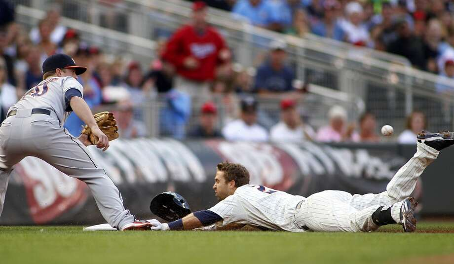 Twins Brian Dozier slides safely with a triple off Astros starting pitcher Erik Bedard. Photo: ANDY CLAYTON-KING, Associated Press
