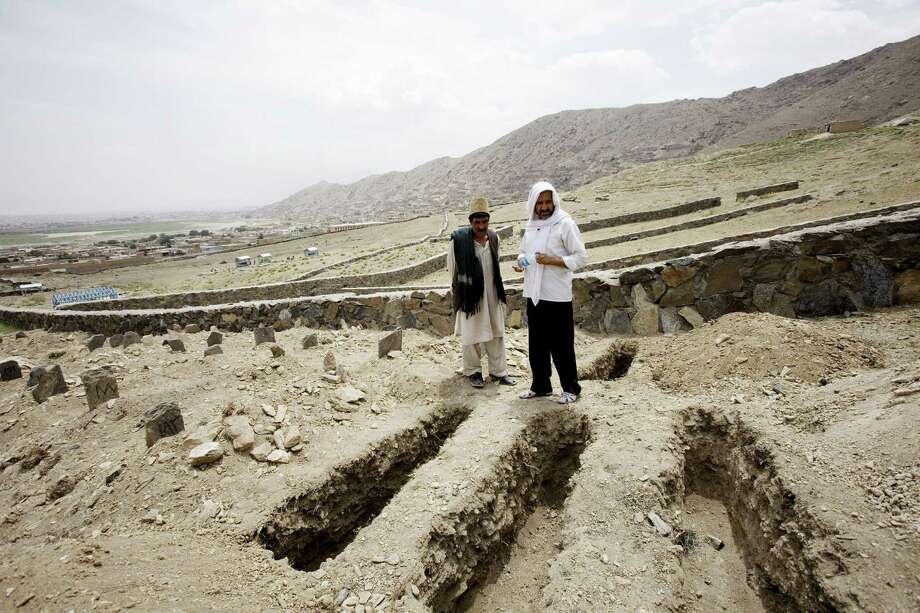 Khwaja Naqib Ahmad (right) and Ghulam Sarwar work at a graveyard in Kabul where the remains of the unclaimed dead, including suicide bombers, are buried. Photo: Christoph Bangert / New York Times