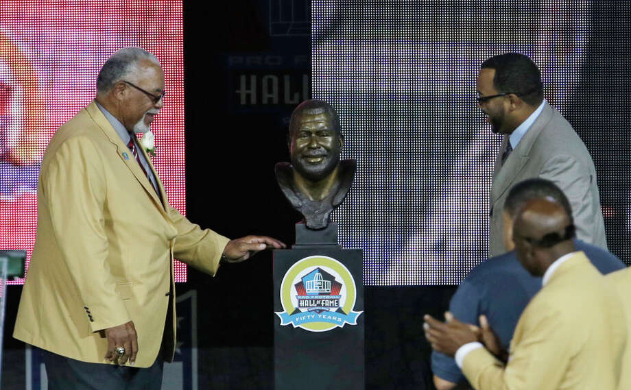 Former Oiler Curley Culp, left, was overjoyed to have his son Chad, right, unveil his bust during the induction ceremony at the Pro Football Hall of Fame on Saturday in Canton, Ohio. Photo: Tony Dejak, STF / AP