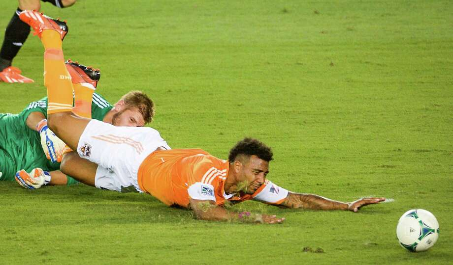 Houston Dynamo midfielder Giles Barnes (23) collides with Columbus Crew goalkeeper Matt Lampson (28) during the first half of MLS soccer match on Saturday, Aug. 3, 2013, at BBVA Compass Stadium in Houston. Barnes was fouled on the play and the Dynamo scored on the ensuing penalty kick. Photo: Smiley N. Pool, Houston Chronicle / © 2013  Houston Chronicle