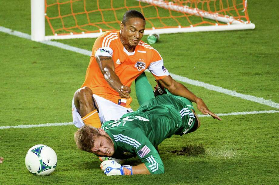 Houston Dynamo midfielder Ricardo Clark (13) collides with Columbus Crew goalkeeper Matt Lampson (28) during the first half of MLS soccer match on Saturday, Aug. 3, 2013, at BBVA Compass Stadium in Houston. Photo: Smiley N. Pool, Houston Chronicle / © 2013  Houston Chronicle