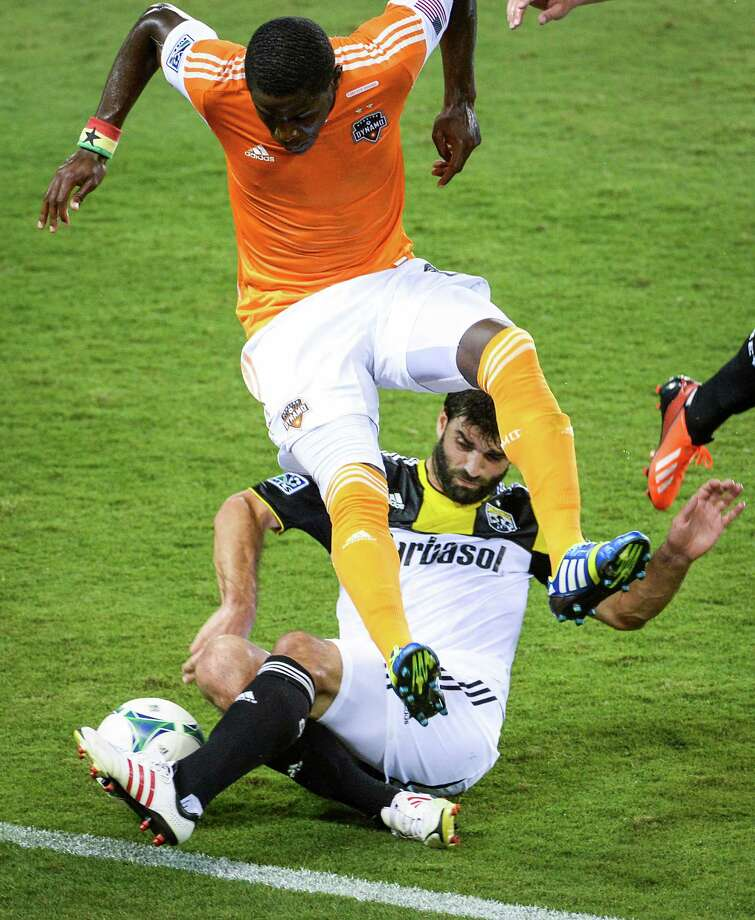 Houston Dynamo defender Kofi Sarkodie (8) leaps over Columbus Crew defender/midfielder Agustin Viana (24) during the first half of MLS soccer match on Saturday, Aug. 3, 2013, at BBVA Compass Stadium in Houston. Photo: Smiley N. Pool, Houston Chronicle / © 2013  Houston Chronicle