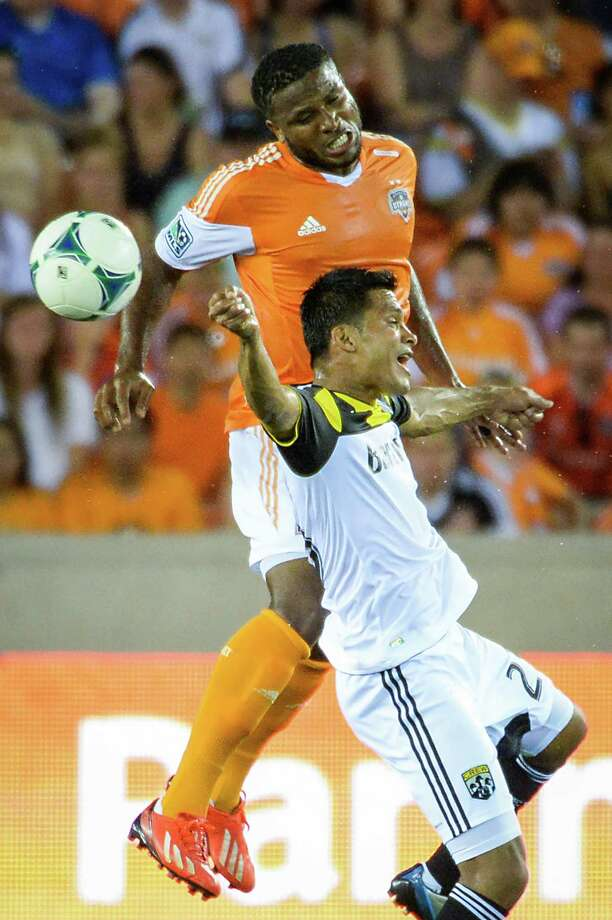 Houston Dynamo defender Jermaine Taylor (4) fights for a header against Columbus Crew forward Jairo Arrieta (25) during the first half of MLS soccer match on Saturday, Aug. 3, 2013, at BBVA Compass Stadium in Houston. Photo: Smiley N. Pool, Houston Chronicle / © 2013  Houston Chronicle