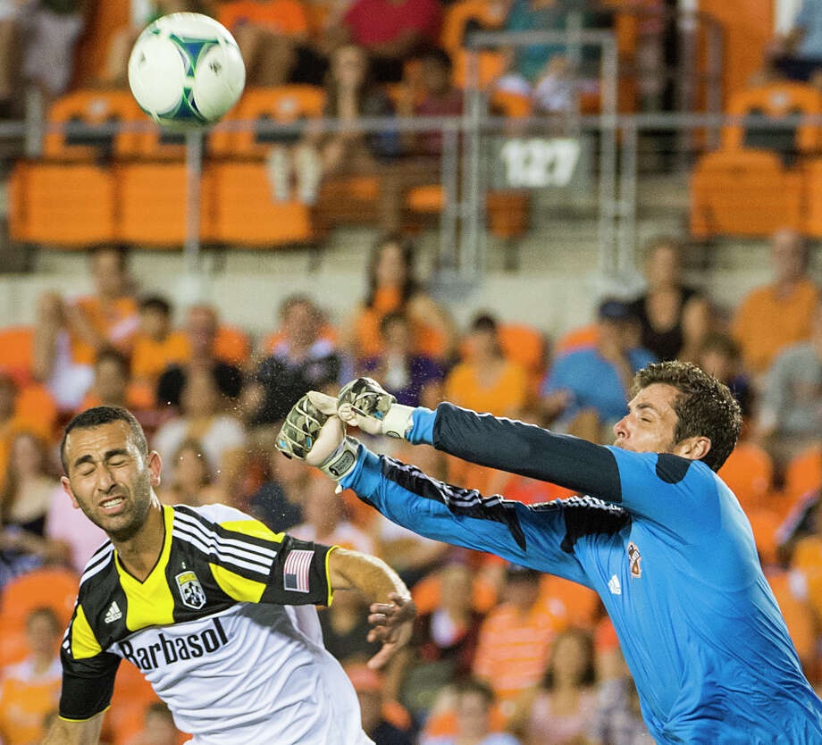 Houston Dynamo goalkeeper Tally Hall punches the ball away from Columbus Crew forward Justin Meram during the second half of MLS soccer match on Saturday, Aug. 3, 2013, at BBVA Compass Stadium in Houston. The Dynamo won the game 3-1. Photo: Smiley N. Pool, Houston Chronicle / © 2013  Houston Chronicle