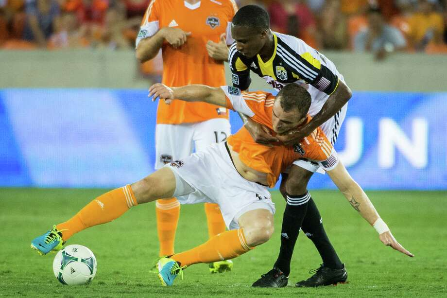 Houston Dynamo forward Cam Weaver is pulled down by Columbus Crew midfielder Kevan George during the second half of MLS soccer match on Saturday, Aug. 3, 2013, at BBVA Compass Stadium in Houston. The Dynamo won the game 3-1. Photo: Smiley N. Pool, Houston Chronicle / © 2013  Houston Chronicle
