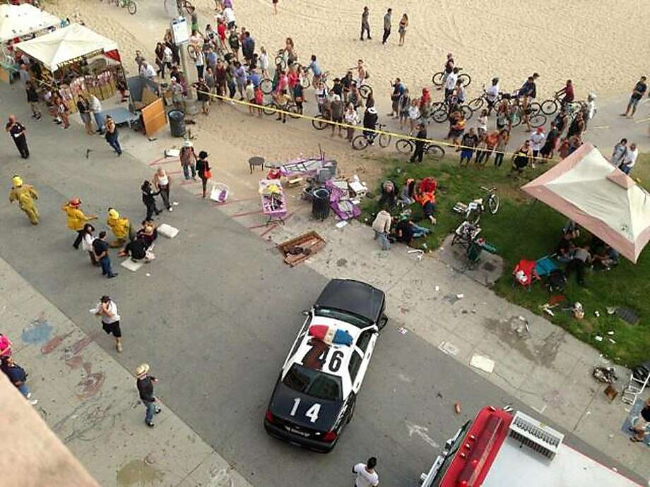 First responders arrive on the scene after a car plowed into the crowded Venice Beach boardwalk and then fled. One person died, and about a dozen others were injured, authorities say. Photo: Maarten Smitskamp, Associated Press
