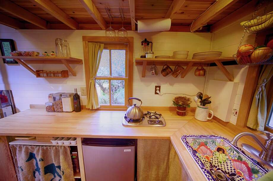 The house has electricity, heat, hot water, a two-burner gas stove, small fridge and kitchen utensils. It's based on a plan from the Tumbleweed Tiny House Company.  Photo: Via Airbnb / © 2012 Christopher Tack