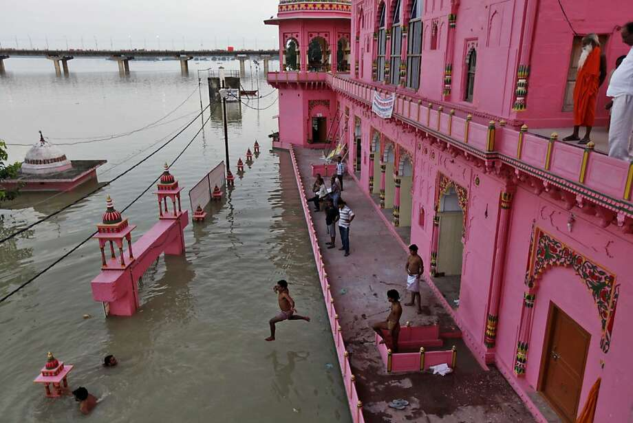 An Indian man jumps to cool off from a residential building partly submerged in the flooded River Ganges after heavy monsoon rains in Allahabad, India, Saturday, Aug. 3, 2013. India's monsoon season, which runs from June through September, brings rains that are vital to agriculture but also cause floods and landslides. (AP Photo/Rajesh Kumar Singh) Photo: Rajesh Kumar Singh, Associated Press