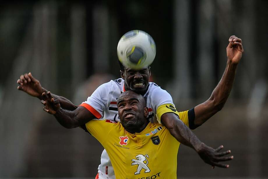 "Lorient's Gabonese defender Bruno Ecuele Manga (C, up) vies with Sochaux' French forward Sloan Privat (C) during the French L1 friendly football match Sochaux vs Lorient on August 3, 2013 at the ""Stade de l'Ill"" stadium in Mulhouse, eastern France. AFP PHOTO / SEBASTIEN BOZONSEBASTIEN BOZON/AFP/Getty Images Photo: Sebastien Bozon, AFP/Getty Images"