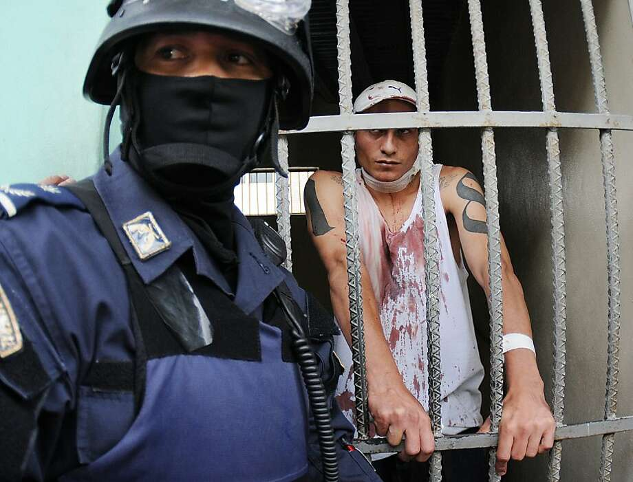 A Honduran police officer guards an injured prisoner, standing inside a cell at the Hospital Escuela, in Tegucigalpa, Honduras, Saturday, Aug. 3, 2013. Honduran President Porfirio Lobo ordered the militarization of the country's main prison on Saturday after a riot there left at least three gang members dead and three guards injured. Police said members of the 18 gang clashed with common criminals in Honduras' National Penitentiary, located 10 miles (15 kilometers) north of the capital.  (AP Photo/Fernando Antonio) Photo: Fernando Antonio, Associated Press