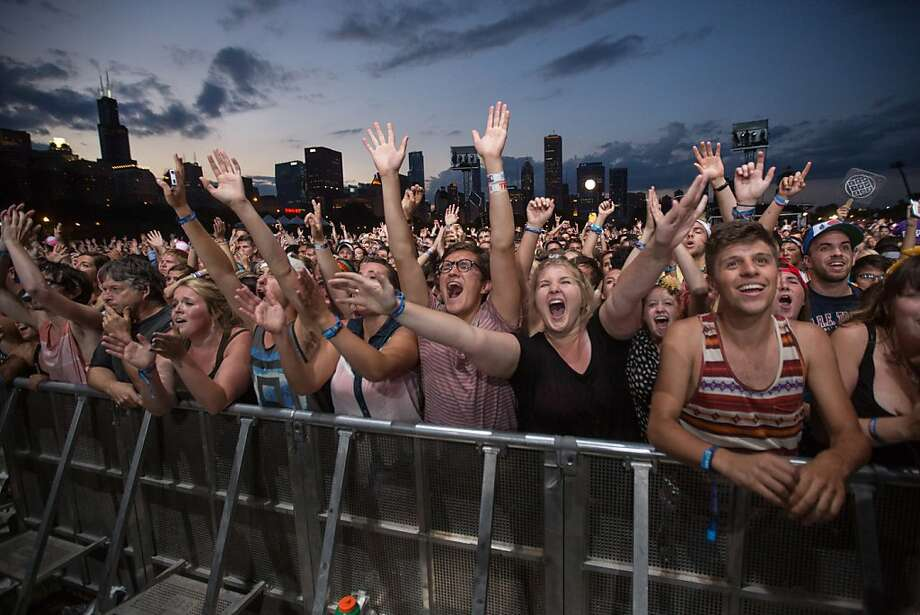 Fans react while Mumford & Sons performs at the Lollapalooza Festival in Chicago, Saturday, Aug. 3, 2013. The more than two-decade-old festival opened Friday in Chicago's lakefront Grant Park. (AP Photo/Scott Eisen) Photo: Scott Eisen, Associated Press