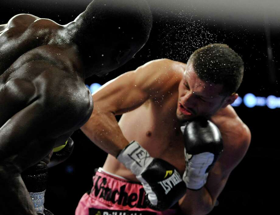 Sweat flies from the head of Andre Berto, left, as he is hit by Jesus Soto Karass, of Mexico, during a welterweight title boxing match, Saturday, July 27, 2013, in San Antonio. Soto Karass won by TKO in the 12th round. (AP Photo/Darren Abate) Photo: Darren Abate, Associated Press / FR115 AP