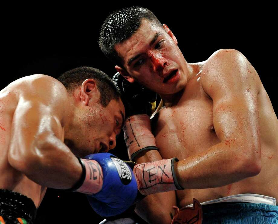 Omar Figueroa, Jr., right, and Nihito Arakawa, of Japan, exchange punches during a lightweight title boxing match, Saturday, July 27, 2013, in San Antonio. Figueroa won by decision after 12 rounds. (AP Photo/Darren Abate) Photo: Darren Abate, Associated Press / FR115 AP