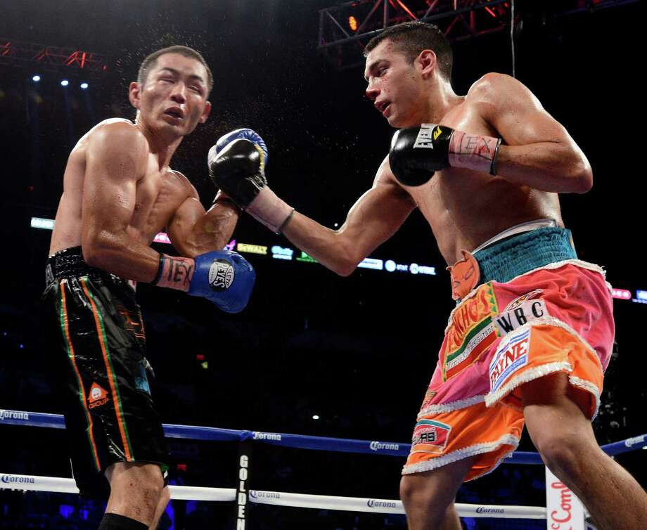 Omar Figueroa, Jr., right, hits Nihito Arakawa, of Japan, during a lightweight title boxing match, Saturday, July 27, 2013, in San Antonio. Figueroa won by decision after 12 rounds. (AP Photo/Darren Abate) Photo: Darren Abate, Associated Press / FR115 AP