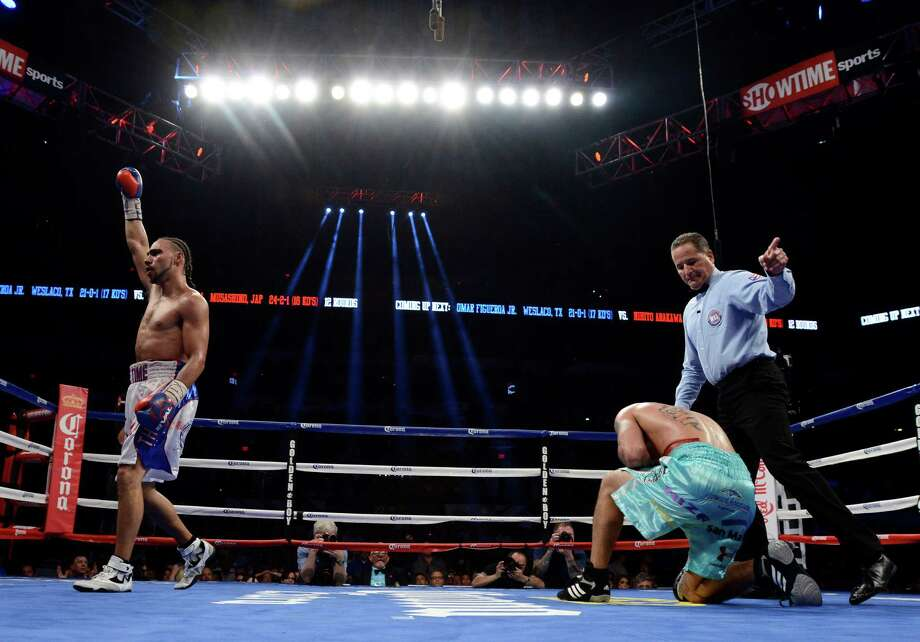 Keith Thurman, left, gestures after knocking down Diego Chaves, of Argentina, in the ninth round, during a welterweight title boxing match, Saturday, July 27, 2013, in San Antonio. Thurman won by KO in the 10th round. (AP Photo/Darren Abate) Photo: Darren Abate, Associated Press / FR115 AP
