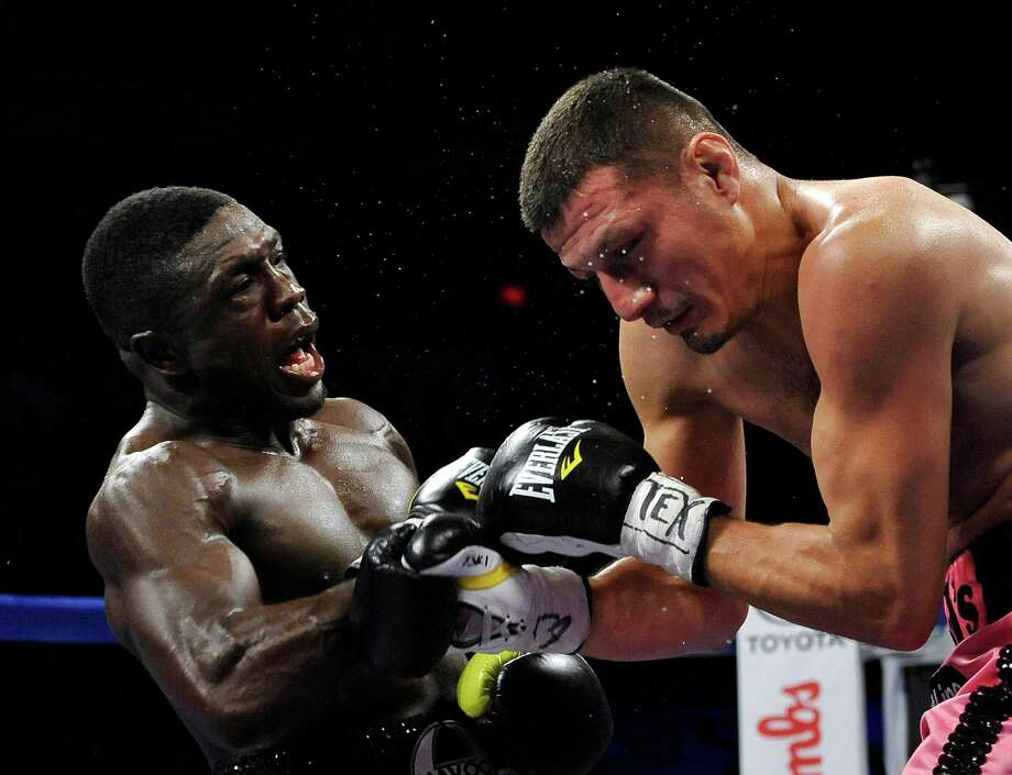 Andre Berto, left, and Jesus Soto Karass, of Mexico, exchange punches during a welterweight title boxing match, Saturday, July 27, 2013, in San Antonio. Soto Karass won by TKO in the 12th round. (AP Photo/Darren Abate) Photo: Darren Abate, Associated Press / FR115 AP