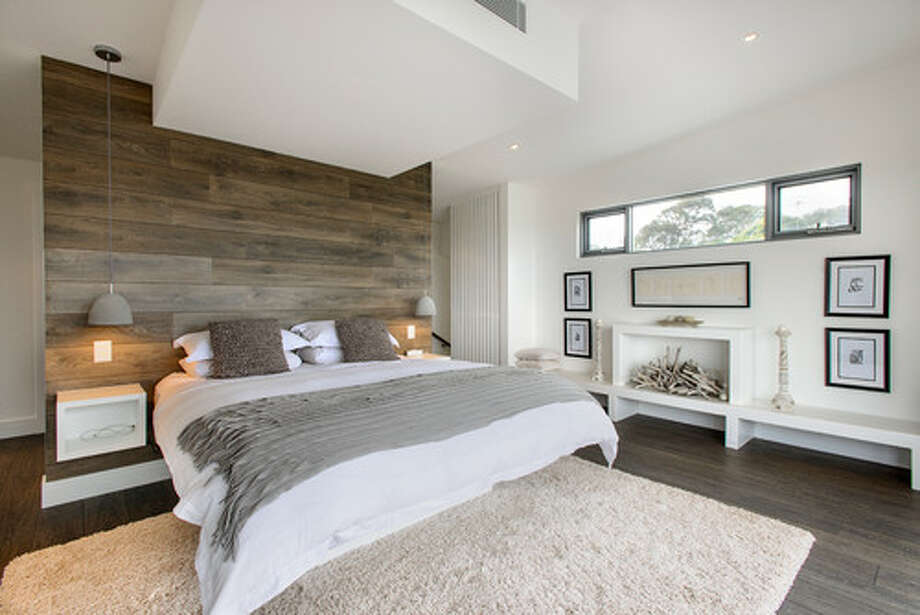 An accent wall made of a material that resembles driftwood creates a focal point in this restful bedroom. The designer plucked subtle accent hues straight from the wall. Photo: Houzz.com