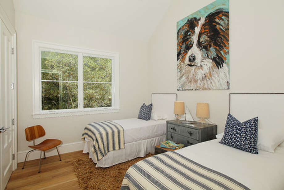An Eames molded plywood chair brings in wood and metal textures and midcentury style in this quiet coastal bedroom. Photo: Houzz.com