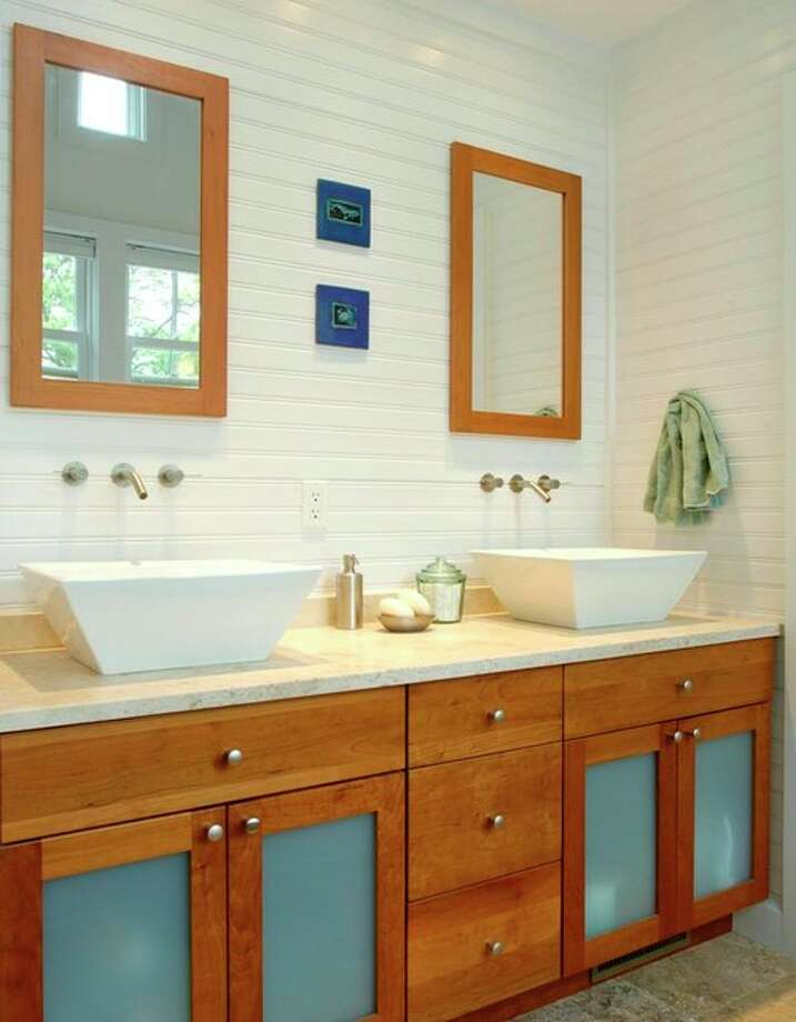 6. Balance whites (and/or off-whites) and warm woods. Cherry cabinetry anchors this beautiful bathroom in avid surfer, paddleboarder and architect Richard Bubnowski's own home. Small accents of the warm wood punctuate the expanse of white walls in the form of mirror frames. Translucent glass cabinet doors resemble sea glass. Photo: Houzz.com