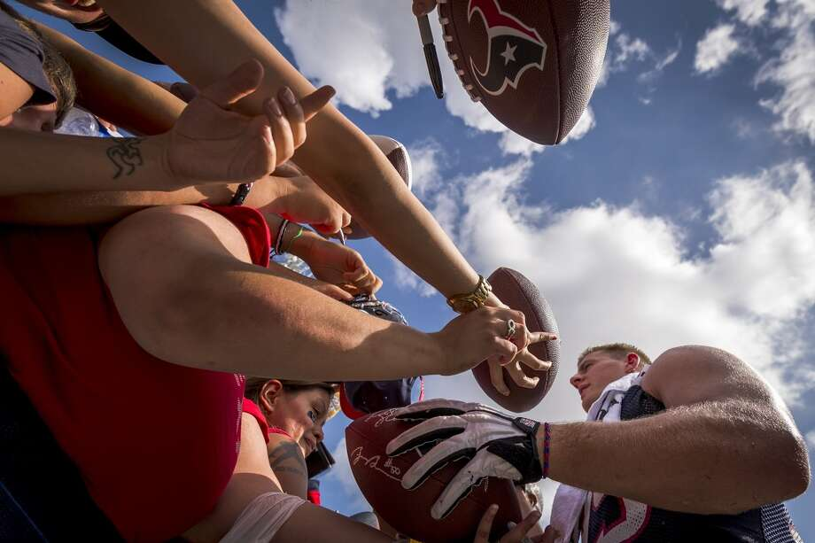 Defensive end J.J. Watt signs autographs after practice. Photo: Smiley N. Pool, Chronicle