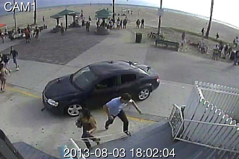 Pedestrians scatter as a car drives through a packed Saturday afternoon crowd along the Venice Beach boardwalk in Los Angeles in this frame from security camera footage. The hit-and-run killed a woman and injured 11 others. Photo: Uncredited, Associated Press