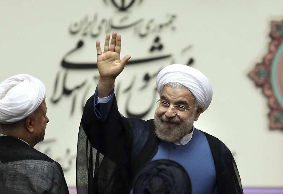 Iran's new president, Hasan Rouhani, waves after taking the oath of office in parliament in Tehran. The moderate cleric won a landslide victory in June. Photo: Ebrahim Noroozi, Associated Press