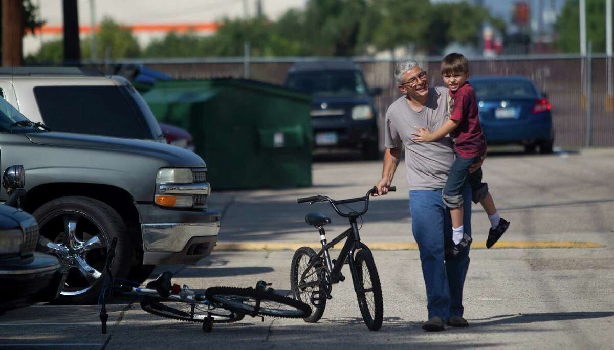 """""""Are you okay? You'll be alright,"""" Frank Lowrance, 50, said as he rushed over on his bike to comfort his son, Noah, 8, who had just crashed on his bike outside their apartment Wednesday, July 31, 2013, in Spring. Noah's mother left him when he was seven months old, leaving Frank, at the age of 42, to take over as a single father. """"I thought, 'okay God, how am I going to do this?'"""" Lowrance said. """"To me it's a privilege,"""" he said. """"I didn't grow up to be an astronaut. But I got to be a cool dad and that's better than anything."""""""