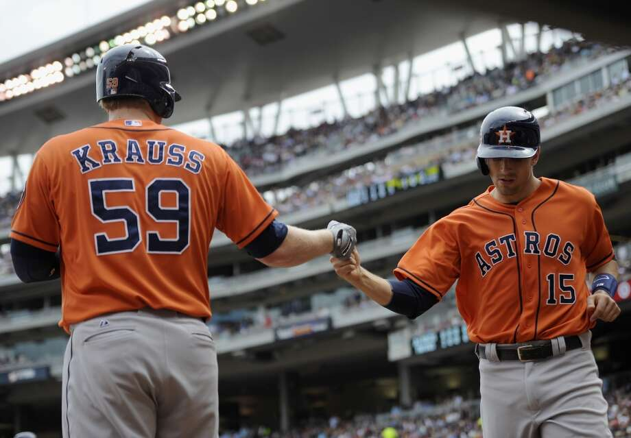 Marc Krauss, left, congratulates teammate Jason Castro on scoring a run during the fifth inning. Photo: Hannah Foslien, Getty Images