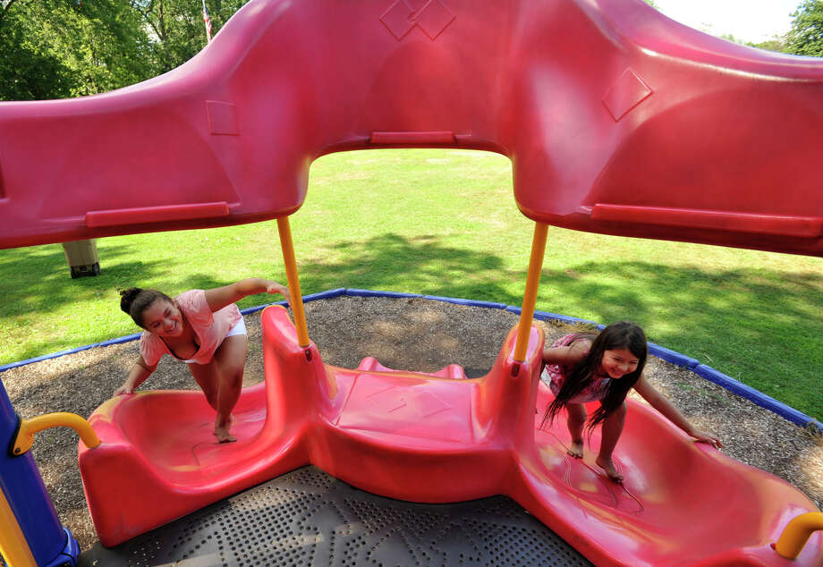 Heidy Cabrera, 13, left, and her sister, Melonie, 6, climb the slide at Barrett Park in Stamford on Sunday, Aug. 4, 2013. Photo: Jason Rearick / Stamford Advocate