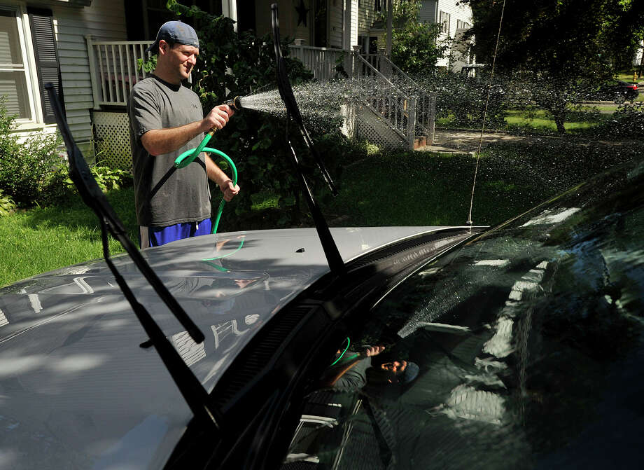 Jeff Hoelderlin washes his car in his driveway in Stamford on Sunday, Aug. 4, 2013. Temperatures on Sunday reached the high 70s. Photo: Jason Rearick / Stamford Advocate