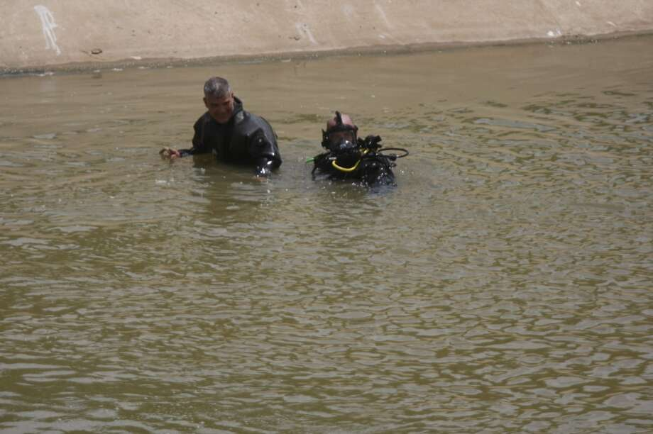 Two children drowned during a family fishing trip at Sims Bayou on Aug. 4, 2013. Rescuers still are searching for a relative who went missing after entering the water to try to rescue the children. (Johnny Hanson/Houston Chronicle)