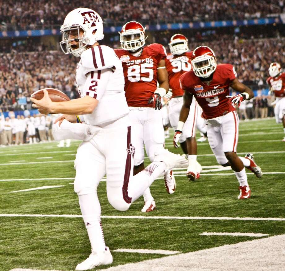 Texas A&M quarterback Johnny Manziel evades Oklahoma defenders during the Cotton Bowl. Photo: Nick De La Torre, Houston Chronicle