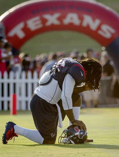 Safety D.J. Swearinger kneels in prayer before practice.