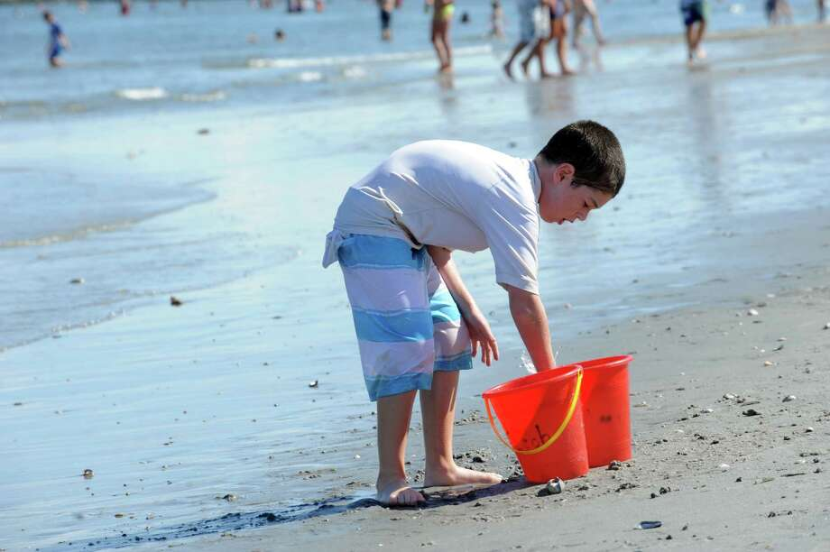 Jacob Leibowitz, 7, of Cos Cob, playing with two buckets at Greenwich Point Park in Greenwich, Conn., Sunday, August 4, 2013. Photo: Helen Neafsey / Greenwich Time