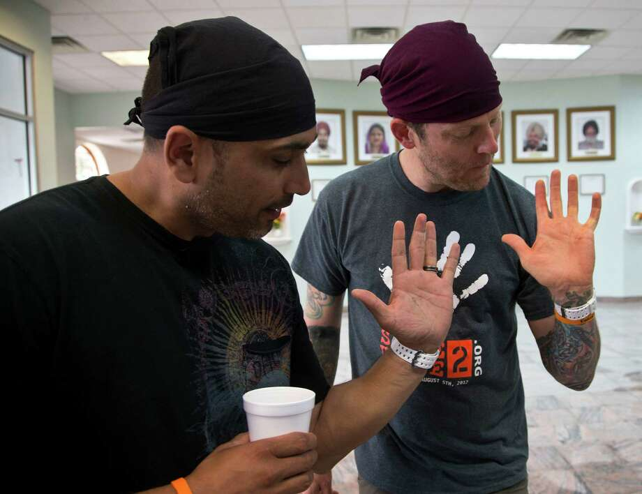 Pardeep Kaleka, left, son of a shooting victim, and Arno Michaelis, an ex-skinhead, show their matching tattoos at the Sikh Temple of Wisconsin in Oak Creek. Photo: Morry Gash, STF / AP
