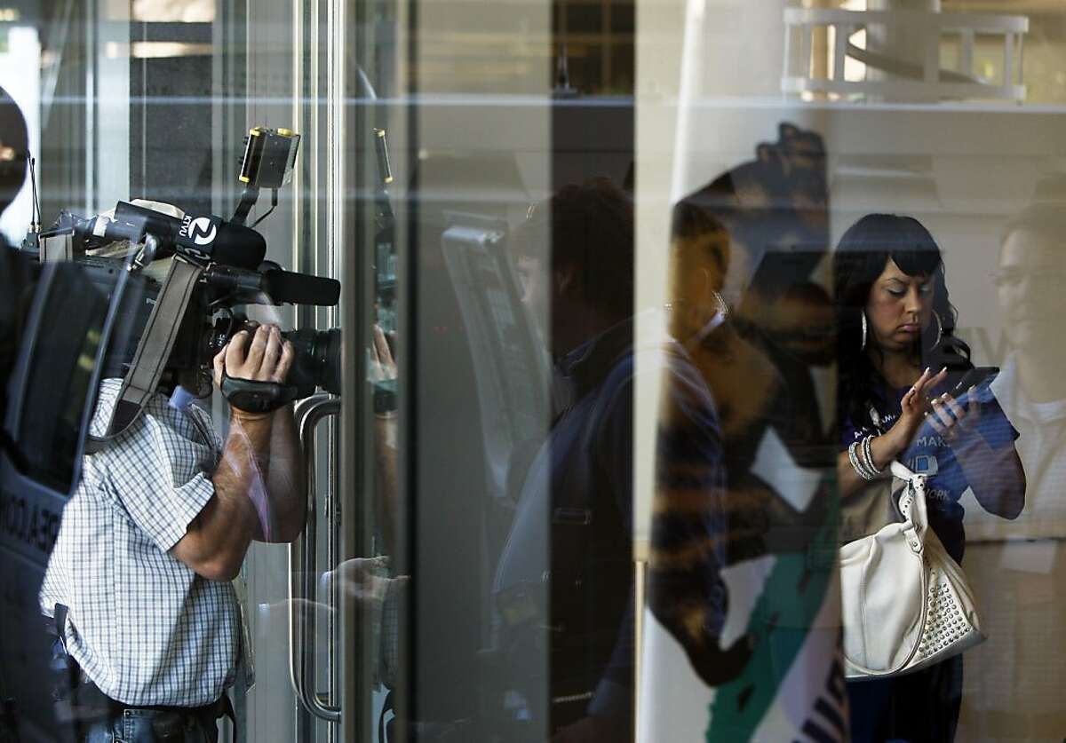 Union members congregate in the lobby while TV crews try to capture some footage while waiting for news on the negotiations at the Department of transportation building on Sunday, August 04, 2013 in Oakland, Calif.