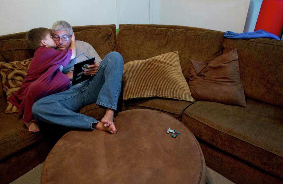 Noah, 8, gives his father, Frank Lowrance, 50, a kiss before bed in the one-bedroom apartment they share in Spring. Photo: Johnny Hanson, Staff / © 2013  Houston Chronicle