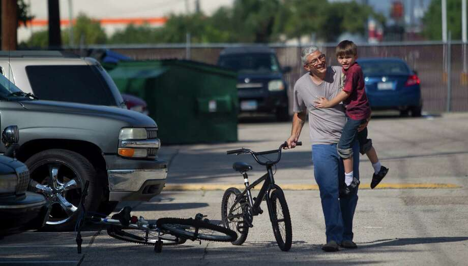"""""""You'll be all right,"""" Frank Lowrance says as he comforts his son, Noah, who crashed on his bike at their home in Spring. In Harris County, single dads like Lowrance head nearly 39,500 household, according to the census. Photo: Johnny Hanson, Staff / © 2013  Houston Chronicle"""