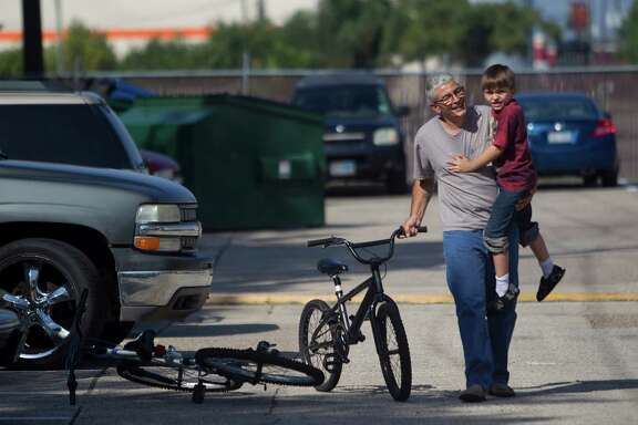 """""""You'll be all right,"""" Frank Lowrance says as he comforts his son, Noah, who crashed on his bike at their home in Spring. In Harris County, single dads like Lowrance head nearly 39,500 household, according to the census."""