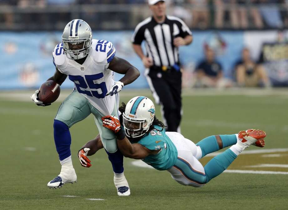 Dallas Cowboys running back Lance Dunbar (25) runs the ball for 11 yards as Miami Dolphins outside linebacker Philip Wheeler (52) misses a tackle in the first quarter at the Pro Football Hall of Fame exhibition NFL football game, Sunday, Aug. 4, 2013, in Canton, Ohio. (AP Photo/Tony Dejak) Photo: Tony Dejak, Associated Press
