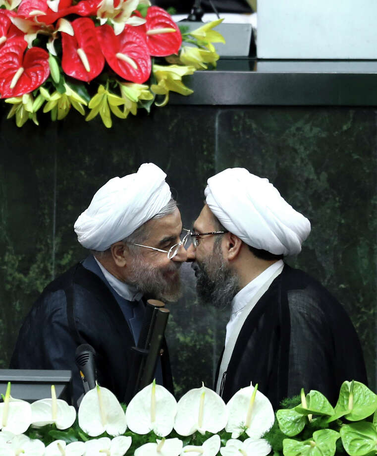 "Iran's new President Hasan Rouhani, left, and judiciary chief Sadeq Larijani, greet each other after Rouhani swore-in at the parliament, in Tehran, Iran, Sunday, Aug. 4, 2013. Iran's new president on Sunday called on the West to abandon the ""language of sanctions"" in dealing with his country over its contentious nuclear program, hoping to ease the economic pressures now grinding its people. Rouhani spoke after being sworn in as president in an open session of parliament Sunday, capping a weekend that saw him endorsed by Ayatollah Ali Khamenei, Iran's supreme leader. Parliament speaker Ali Larijani, sits top center. (AP Photo/Ebrahim Noroozi) ORG XMIT: ENO106 Photo: Ebrahim Noroozi / AP"