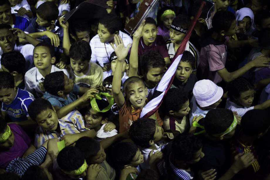 Egyptian children chant slogans against the Egyptian Army during a protest supporting ousted president Mohammed Morsi near Cairo University in Giza. Photo: Manu Brabo / Associated Press