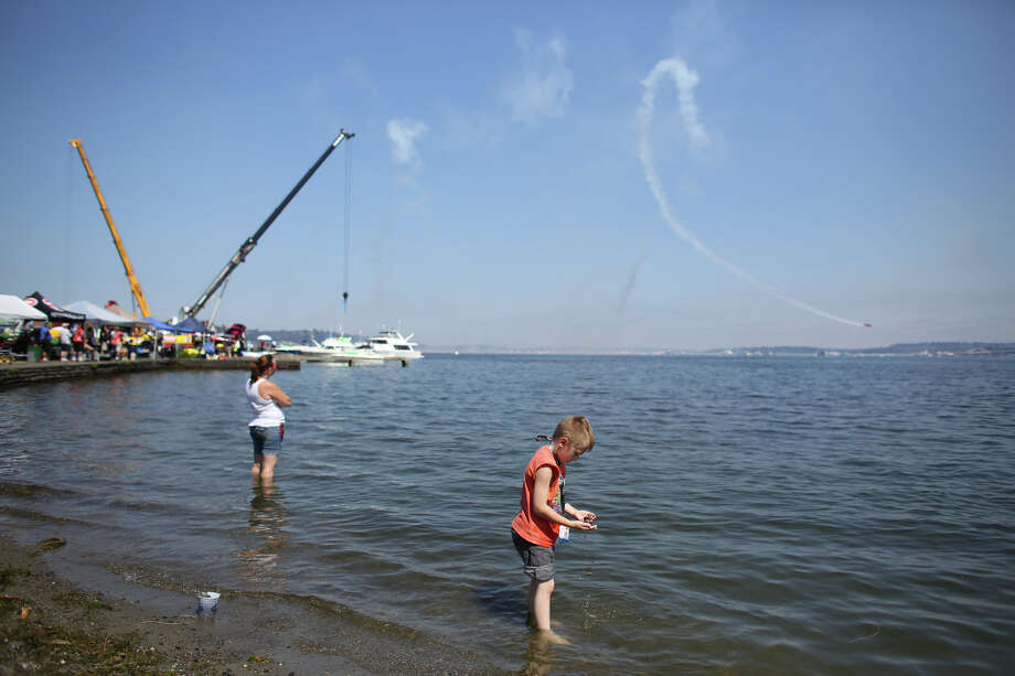 The Lucas Oil Air Show plane performs as people wade into the water. Photo: JOSHUA TRUJILLO, SEATTLEPI.COM / SEATTLEPI.COM