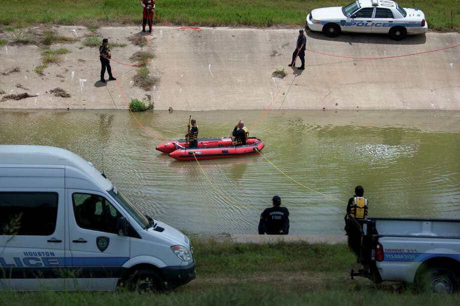 Rescue workers search for an adult uncle who attempted to rescue a 5-year-old and 11-year-old who drowned while the three were fishing in Sims Bayou  on Sunday. The uncle's body was recovered shortly before 3 p.m. Photo: Johnny Hanson, Staff / © 2013  Houston Chronicle