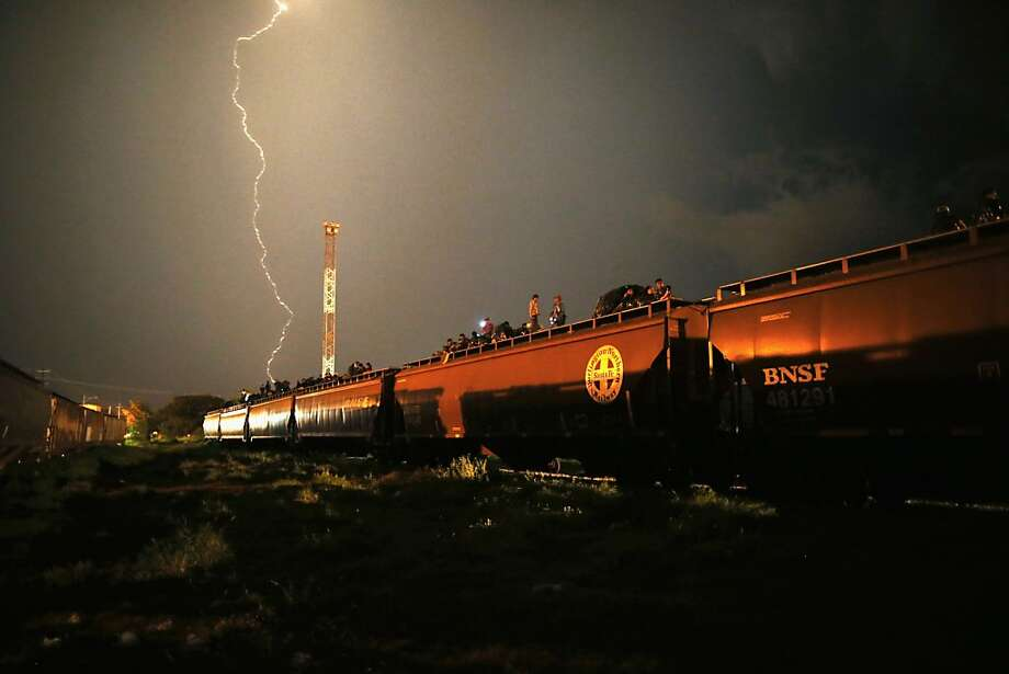 "Dangerous passage: Amid a thunderstorm, Central American migrants ride atop a freight train headed north in Arriaga, Mexico. Thousands of immigrants ride the train, known as la bestia, or ""the beast,"" during their long and perilous journey through Mexico to the U.S. border. Many  are robbed or assaulted by gangs who control the train stops, others fall asleep and tumble off the cars, losing limbs or perishing under the wheels. Photo: John Moore, Getty Images"