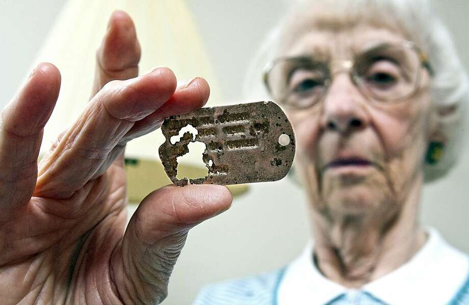 Dead GI's dog tag returned to his sister: Constance Cowan, 87, of Duluth, Minn., examines a dog tag that belonged to her brother, James, who died in the Philippines during World War II. James Cowen, taken prisoner by the Japanese in 1942, was aboard an unmarked POW ship that was bombed by American warplanes in 1944. Some 200 prisoners died in the attack, and Cowen was reported lost at sea. The dog tag ended up in the hands of a tour guide on the island of Corregidor, where James had been stationed. Photo: Clint Austin, Associated Press