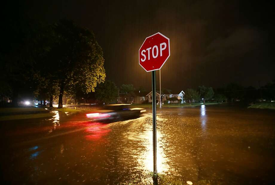 A vehicle makes its way thru a flooded intersection at West 17th Avenue in the early morning hours of Sunday, Aug. 4, 2013, in Hutchinson, Kan. (AP Photo/The Hutchinson News, Lindsey Bauman) Photo: Lindsey Bauman, Associated Press