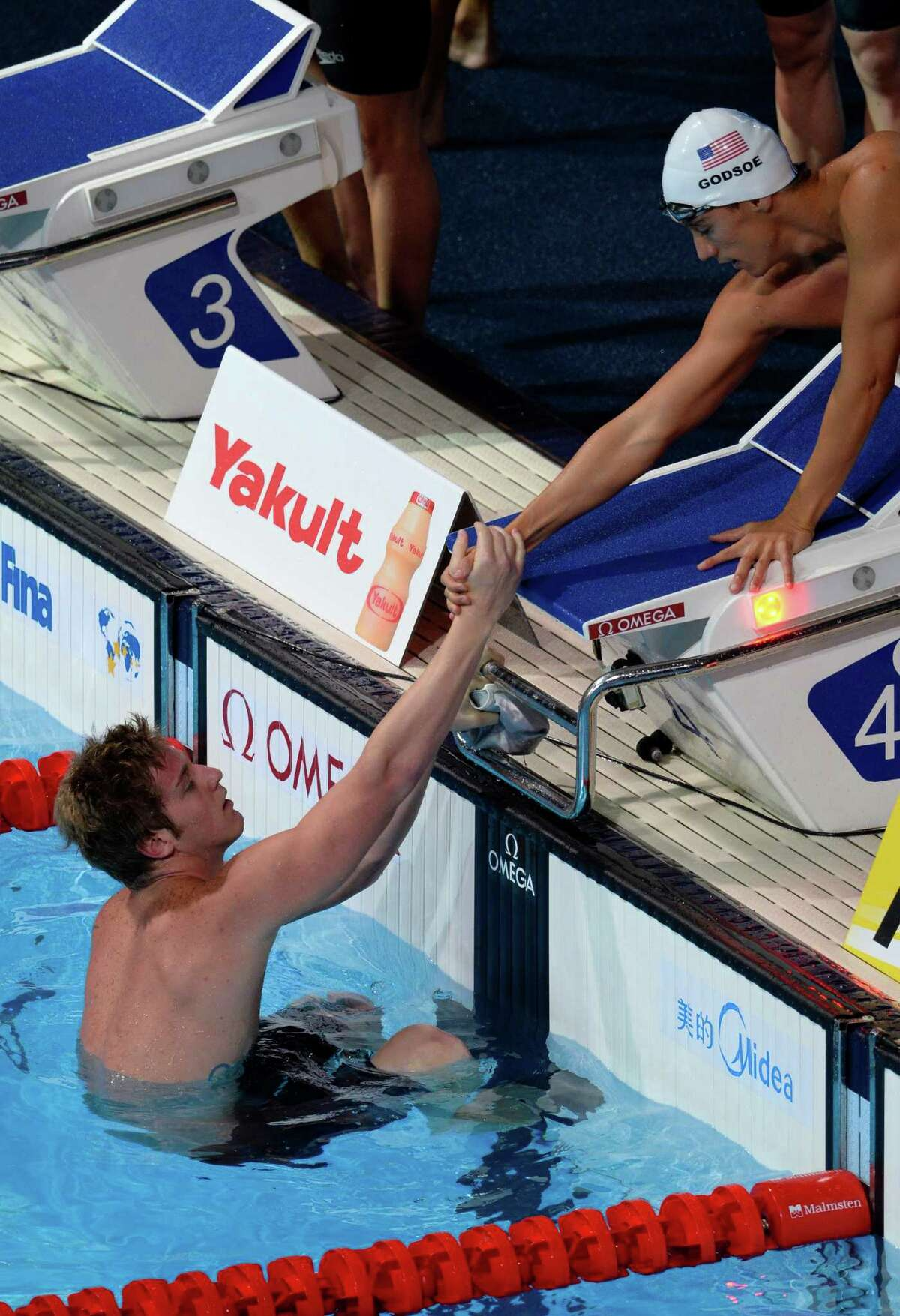 US swimmer Eugene Godsoe (R) shakes hands with US swimmer James Feigen after the heats of the men's 4x100-metre medley relay swimming event in the FINA World Championships at Palau Sant Jordi in Barcelona on August 4, 2013.